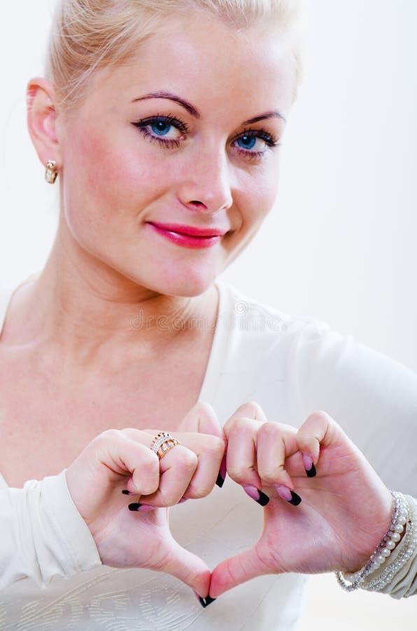 Le femme affiche le coeur de mains photo stock