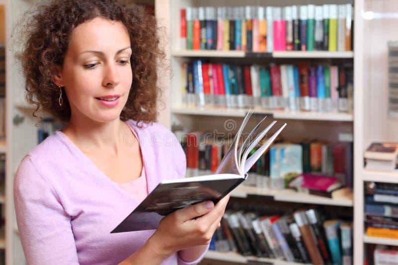 Le femme affiche le livre dans la chambre photographie stock libre de droits