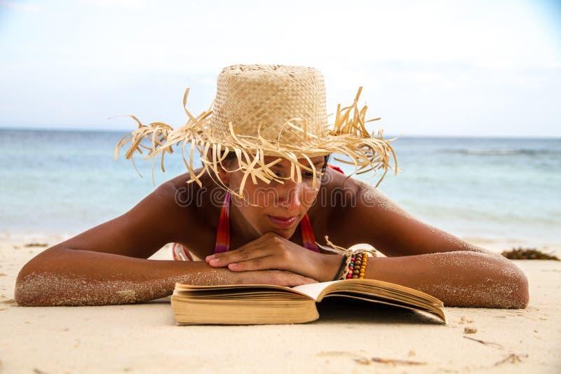 Le femme affiche un livre sur la plage photos libres de droits