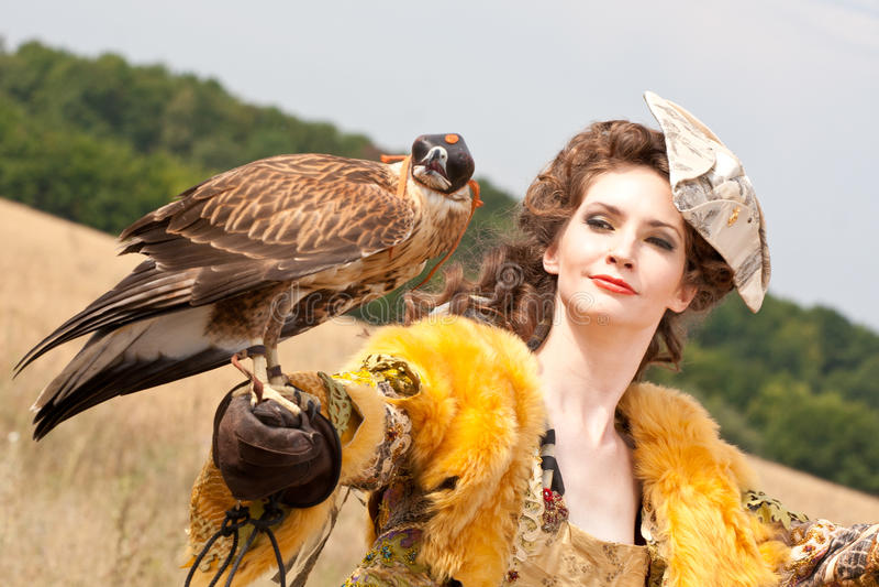 Le femme avec le faucon a un reste photographie stock libre de droits