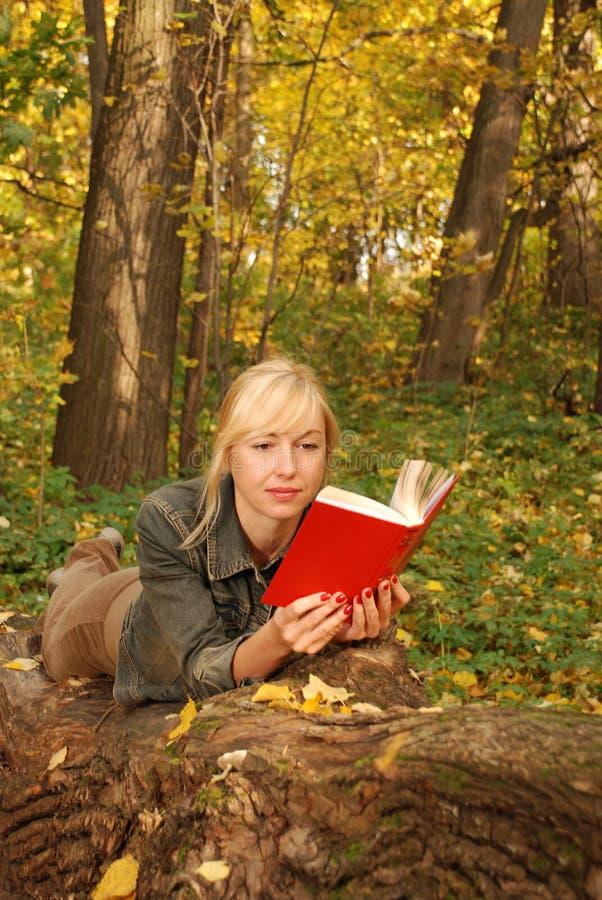 Le femme blond avec un livre s'étend sur l'arbre photo stock
