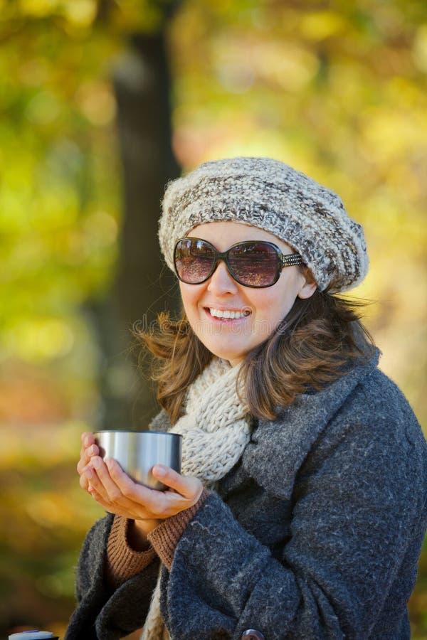 Le femme boit du thé en stationnement d'automne photographie stock