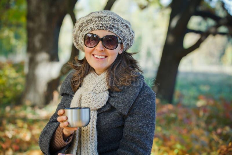 Le femme boit du thé en stationnement d'automne photos stock