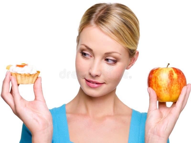 Le femme choisissent du gâteau doux et de la pomme rouge photo libre de droits