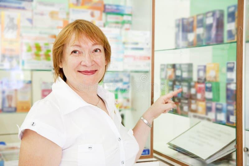 Le femme choisit des contraceptifs à la pharmacie photographie stock libre de droits