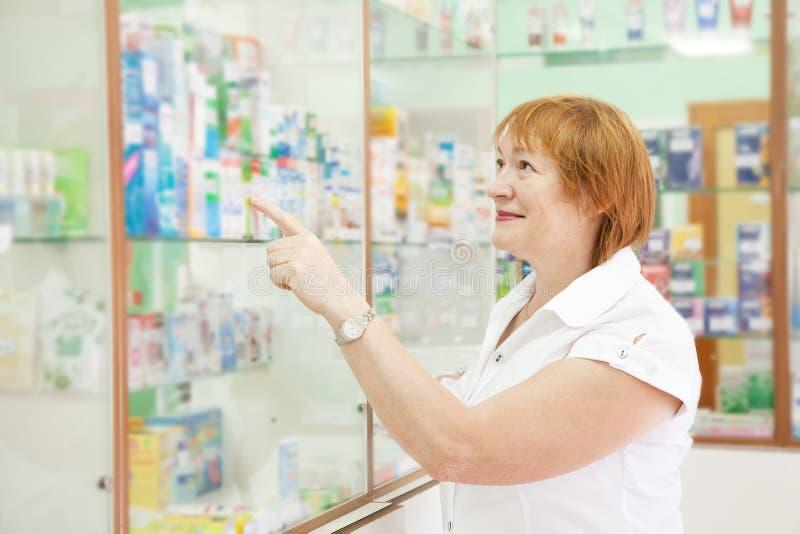Le femme choisit des drogues à la pharmacie images libres de droits