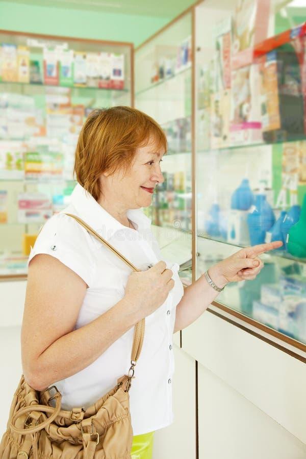 Le femme choisit l'enema à la pharmacie image libre de droits