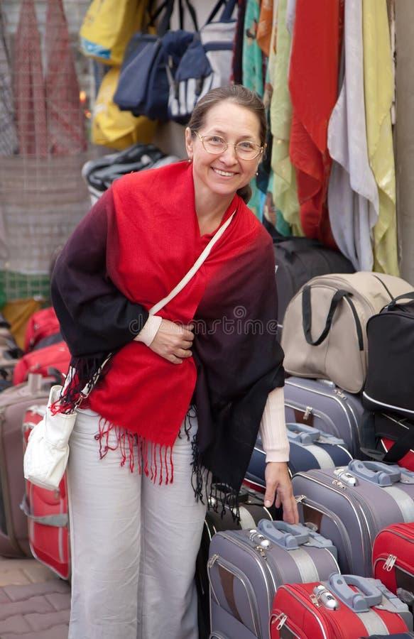 Le femme choisit la valise au système photographie stock
