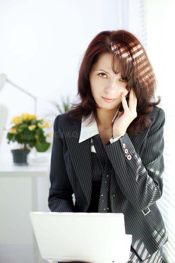 Le femme d'affaires parle au téléphone photographie stock
