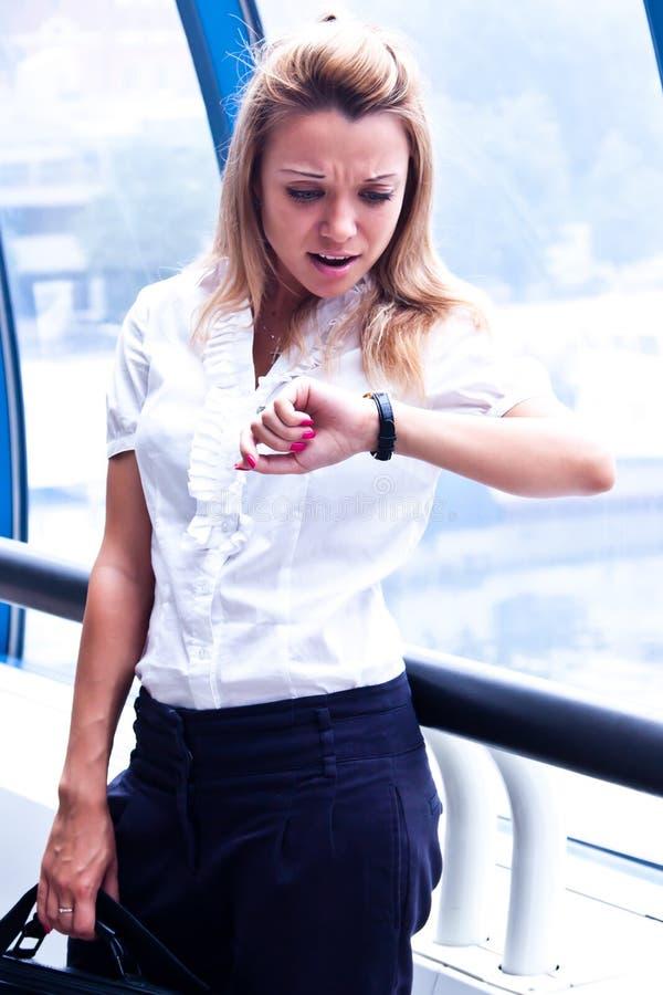 Le femme d'affaires regarde l'horloge photographie stock