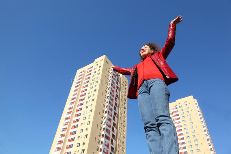 Le femme dans la jupe rouge et des jeans soulève sa main photos stock