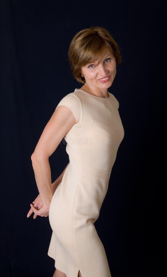 Le femme dans une robe beige image stock
