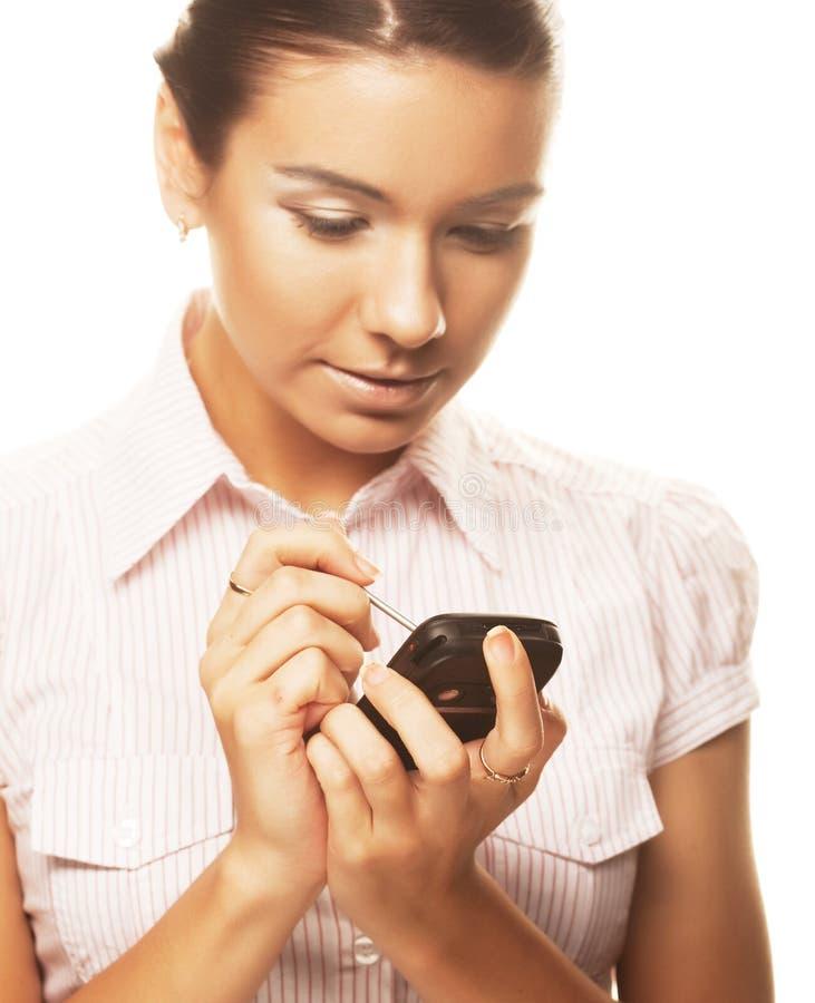 Le femme effectue des notes sur son PDA image stock