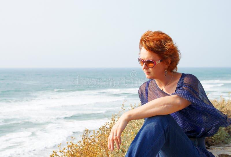 Le femme entre deux âges s'assied par la mer image stock