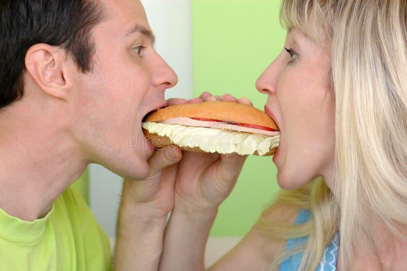 Le femme et l'homme mordent un sandwich photo stock