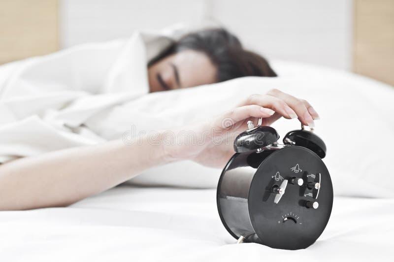 Le femme et l'horloge d'alarme photographie stock libre de droits