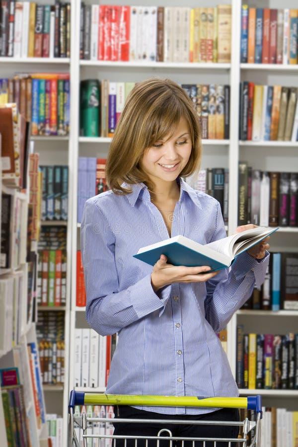 Le femme fait des emplettes dans une librairie images libres de droits