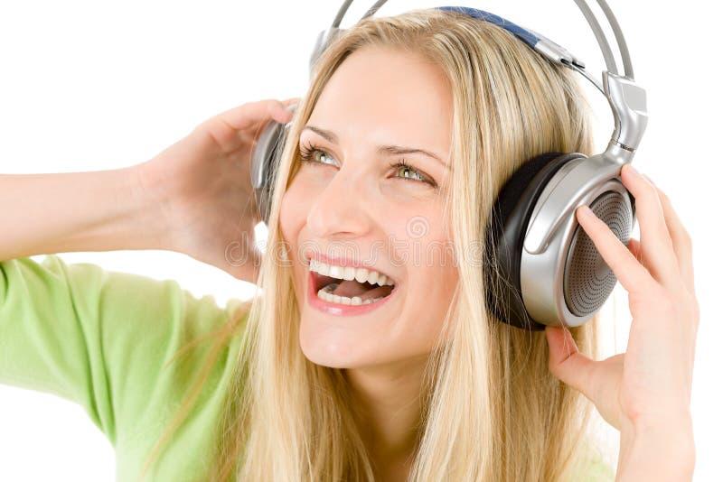 Le femme gai avec des écouteurs écoutent la musique image libre de droits
