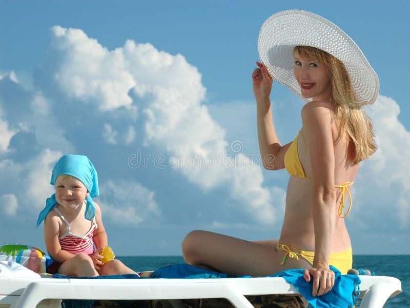 Le femme heureux dans un chapeau blanc et l'enfant s'asseyent image stock