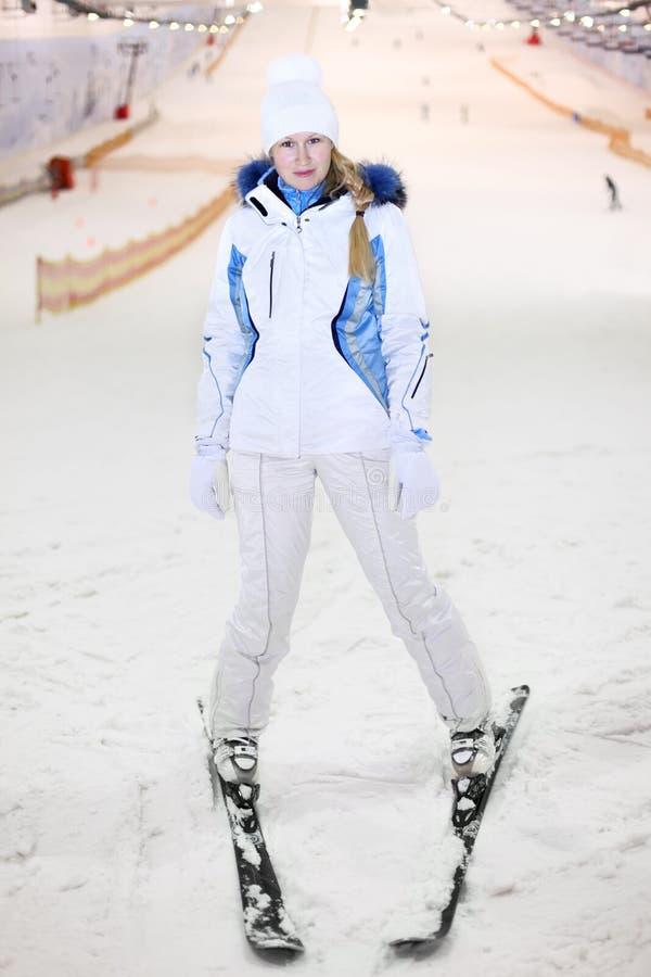 Le femme heureux reste sur le ski dans le ski d'intérieur photos libres de droits
