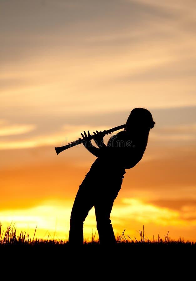 Le femme joue la musique au coucher du soleil. photographie stock