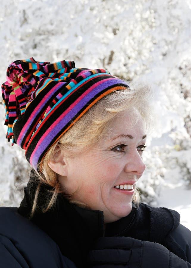 Le femme mûr a empaqueté vers le haut dans la neige image libre de droits