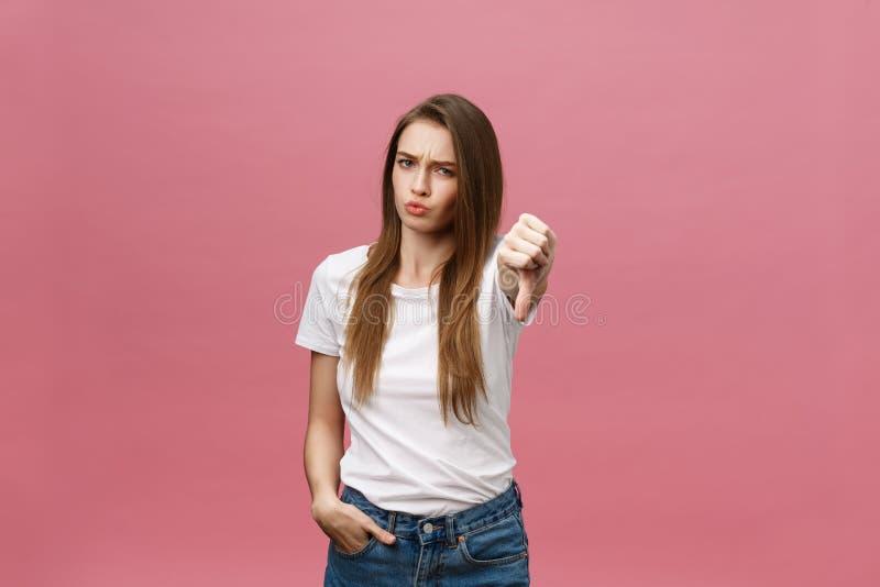Le femme malheureux donnant des pouces font des gestes vers le bas le regard avec l'expression et la désapprobation négatives photographie stock libre de droits
