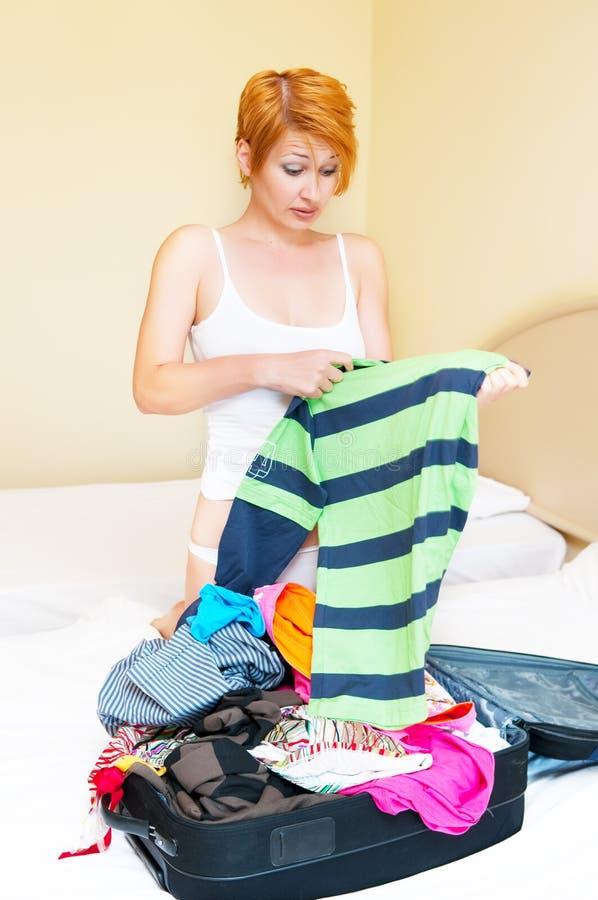Le femme met des vêtements dans la valise. images stock