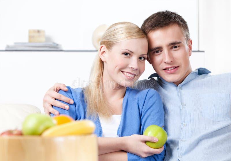 Le femme offre une pomme à son mari photographie stock