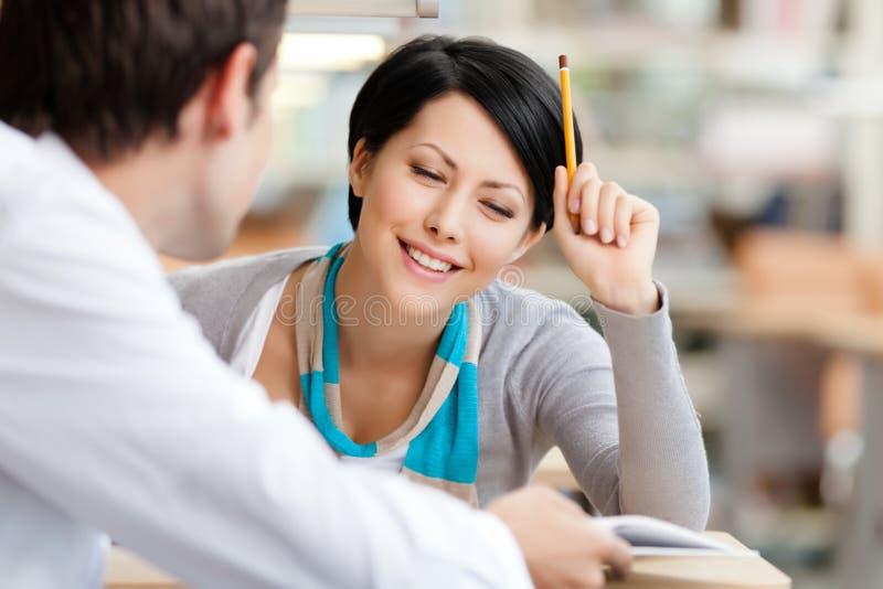 Le femme parle avec l'homme à la bibliothèque photos stock