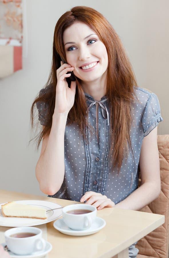 Le femme parle du téléphone au restaurant photo stock