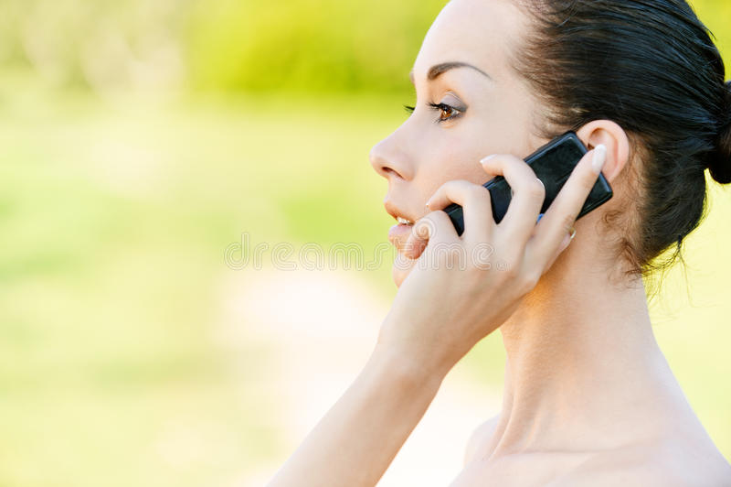 Le femme parle par le téléphone portable photographie stock