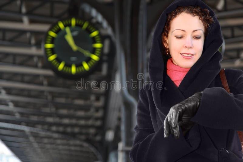 Le femme regarde la montre-bracelet, restant sur la gare photographie stock libre de droits