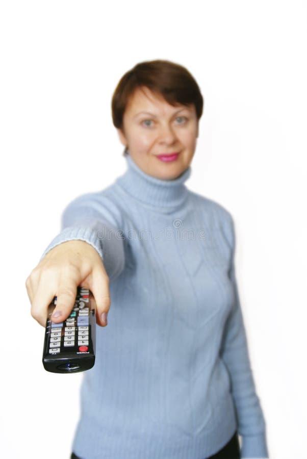 Le femme retient un à télécommande images stock