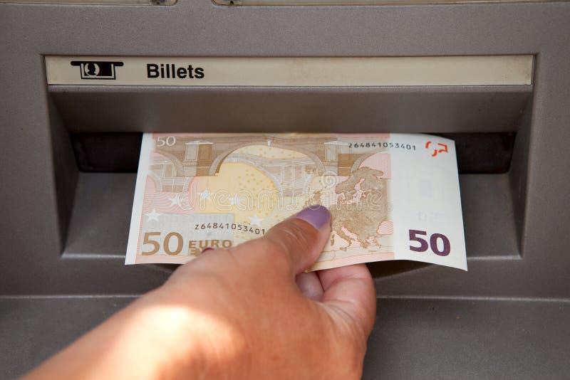 Le femme retirent l'argent aux cashpoints photos stock