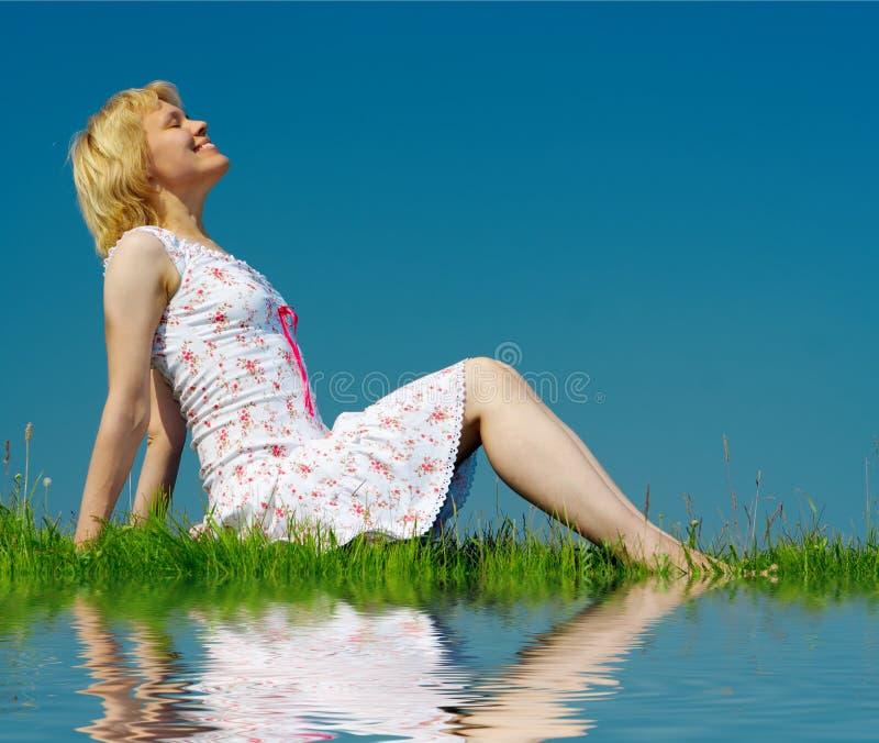 Le femme s'asseyent sur l'herbe verte photo stock