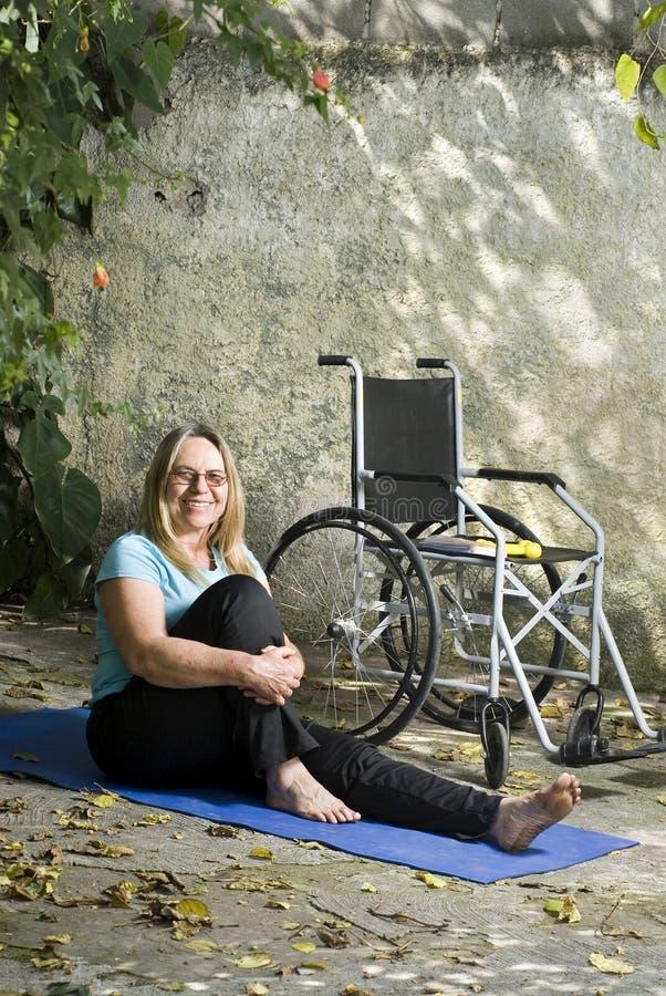 Le femme s'assied sur la verticale de sourire de couvre-tapis de yoga photographie stock
