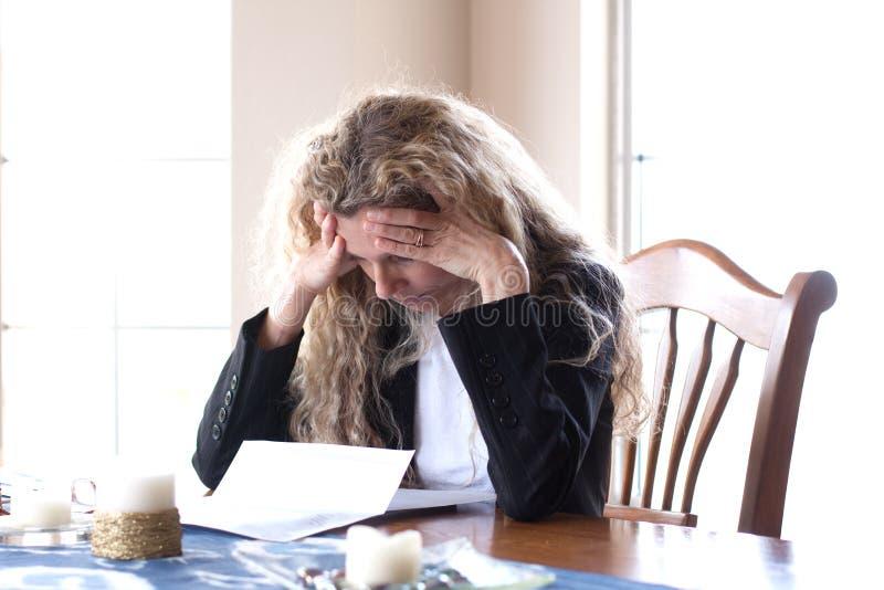 Le femme s'est inquiété des factures et du mal de tête images stock