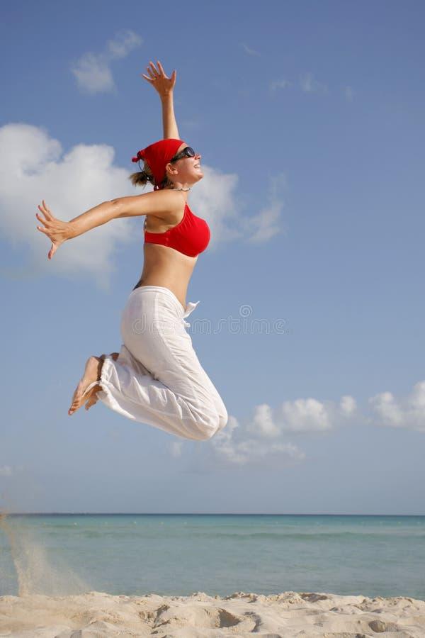 Le femme sautant sur la plage photos stock