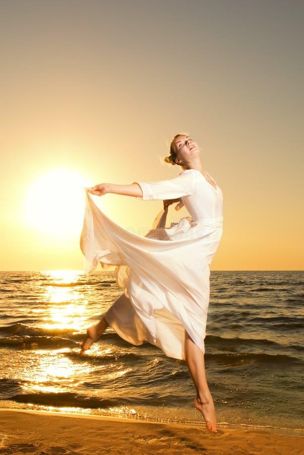 Le femme sautant sur une plage images stock