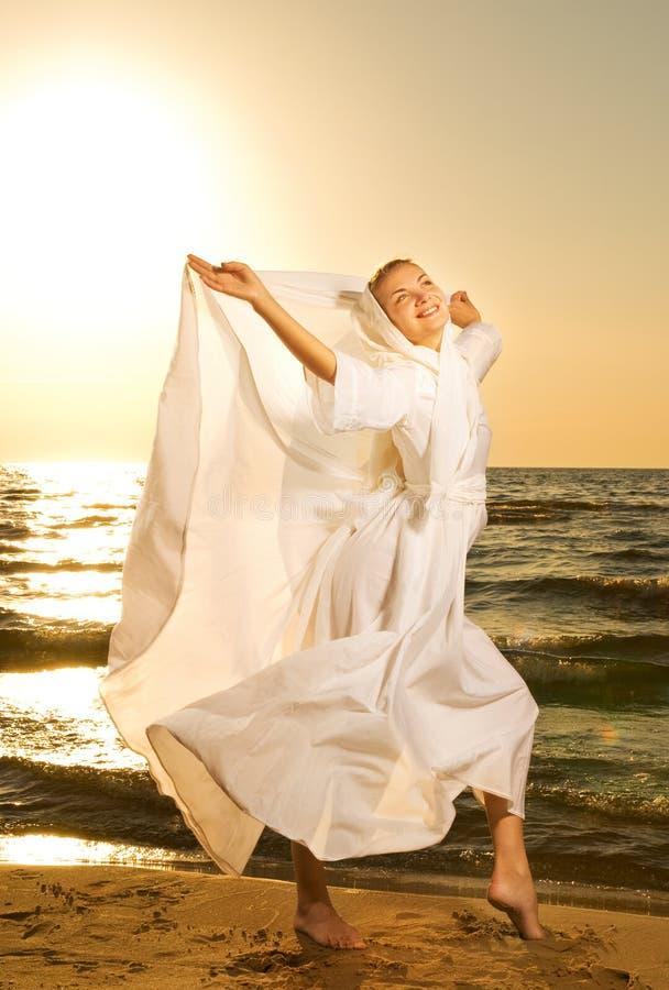 Le femme sautant sur une plage photographie stock libre de droits