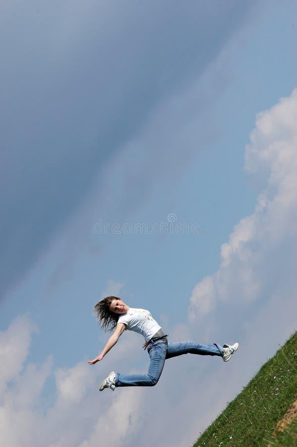 Le femme sautent par-dessus une zone d'herbe photo stock