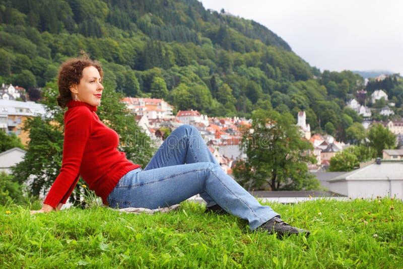 Le femme se trouve sur l'herbe au fond de la ville de Bergen photo stock
