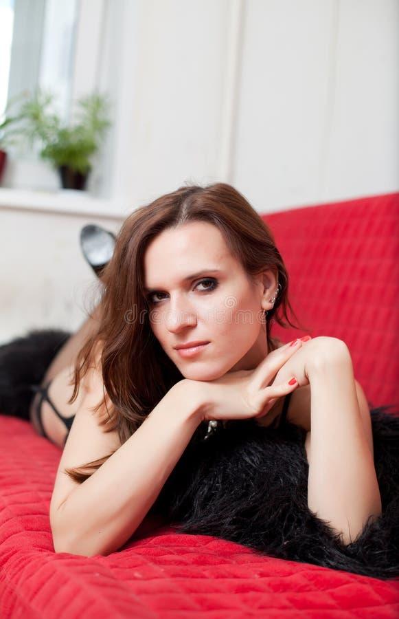 Le femme se trouve sur un sofa photographie stock libre de droits