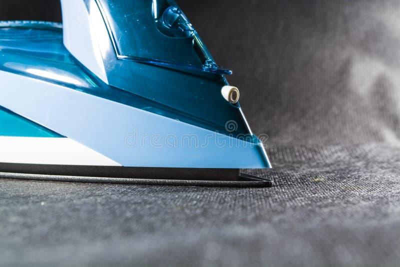 Le fer bleu pour repasser des vêtements Fond noir monophonique appareils électroménagers L'électronique Technologies modernes photo stock