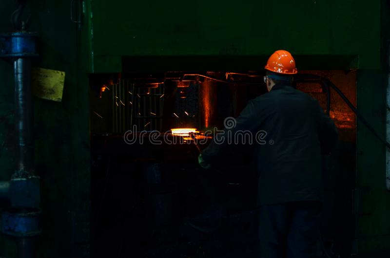 Le fer chaud dans le smeltery s'est tenu par un travailleur Usine pour la production de l'acier photo stock