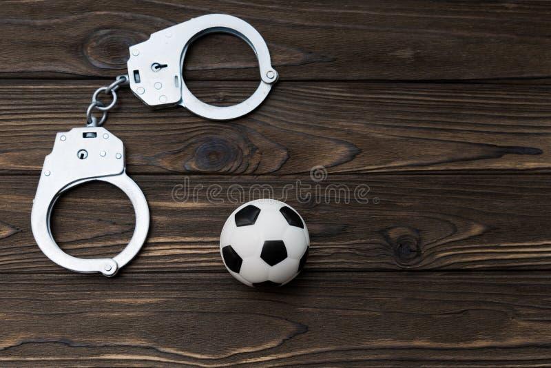 Le fer menotte pour la détention des criminels, un ballon de football sur un fond en bois photos libres de droits