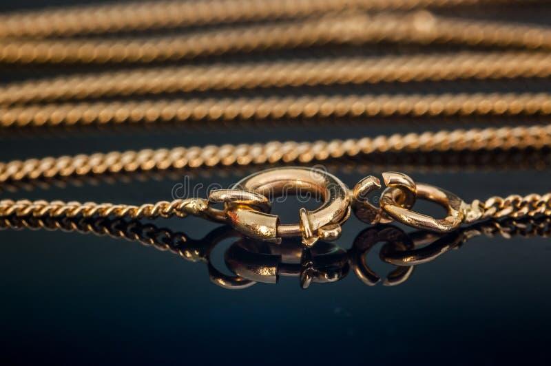Le fermoir ou la fermeture de chaîne de collier d'or s'est fermé sur la table en verre se reflétante photo stock