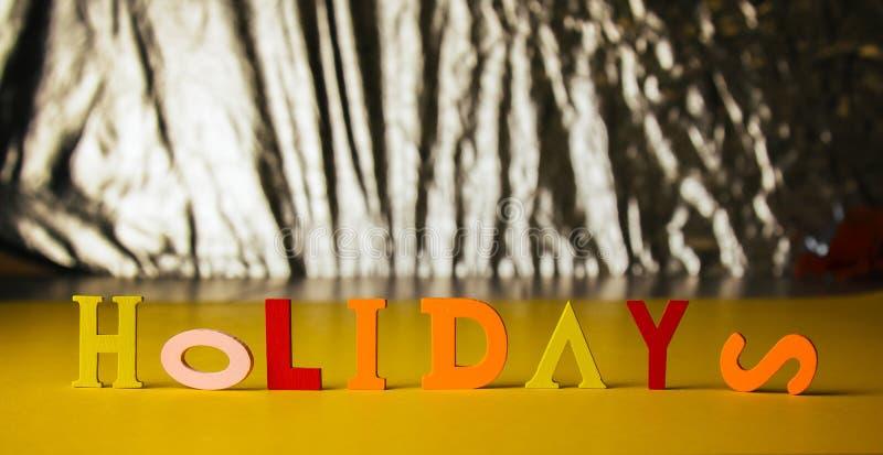 Le feste dell'iscrizione dalle lettere di legno luminose variopinte si trovano su un fondo luminoso immagine stock libera da diritti