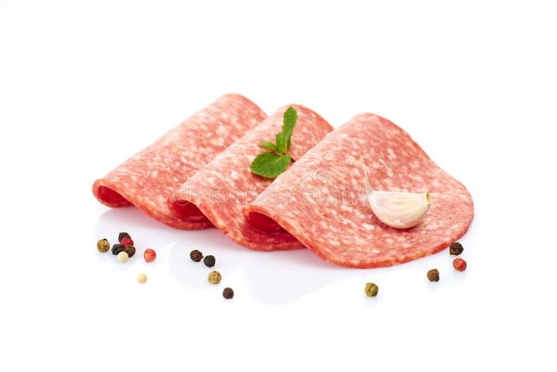 Le fette affumicate della salsiccia hanno isolato il bianco fotografie stock